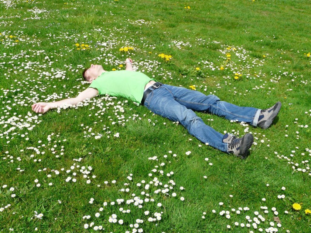A person lying on top of a grass covered field